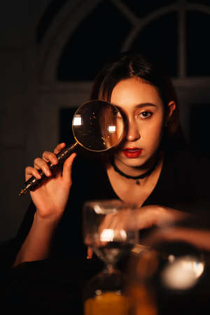 Beautiful young long hair woman fortune teller with crystal ball in dark room.