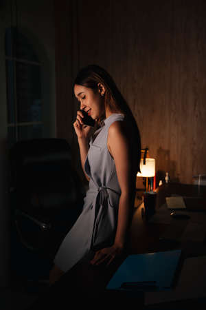 Beautiful mixed race woman using smartphone at night in office.