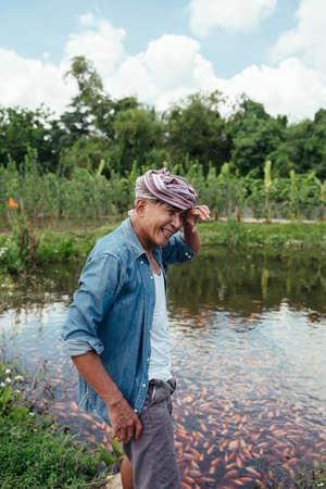 Asian elderly senior farmer standing near fishing pond in country side field. Stock Photo