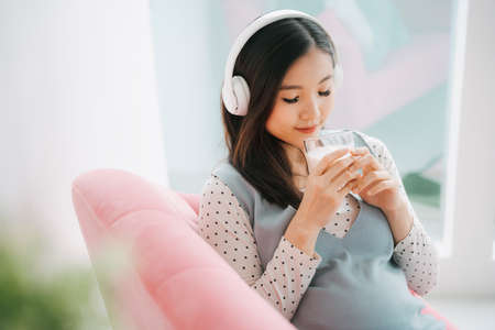 Young beautiful pregnant asian woman listen to musich with wireless headphone and drinking milk at home.