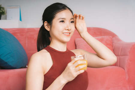 Beautiful pregnant asian woman drinking orange juice after exercise at home.