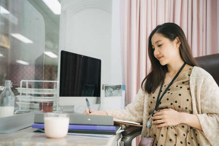 Beautiful pregnant adult asian thai businesswoman working in office.