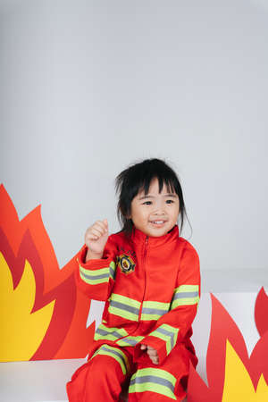 Pretty asian thai kid in firefighter uniform.