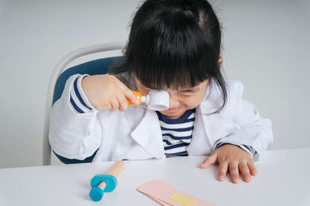 Pretty asian thai kid play role as a dentist using magnifying glass.