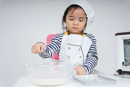 Pretty asian thai kid play role as a chef putting mixed flour into baking plate