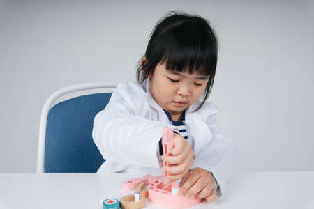 Pretty asian thai kid play role as a dentist fixing teeth toy.