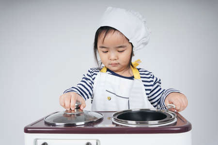 Pretty asian thai kid play role as a chef cooking food at cooker station with oven. Stockfoto