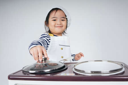 Pretty asian thai kid play role as a chef cooking food at cooker station with oven.