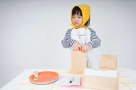 Pretty asian thai kid play role as a waitress wearing yellow bandage packing food in paper bag.