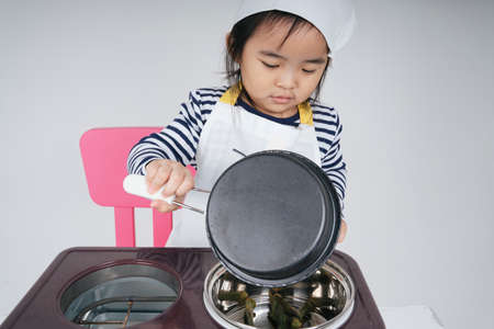 Pretty asian thai kid play role as a chef cooking food at stove station.