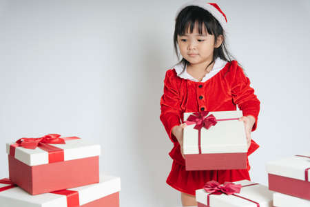 Pretty asian thai kid woman in santa claus uniform with christmas gift box to celebrate snow festival.