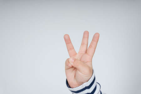 Kid hand with three fingers gesture isolate over white background.