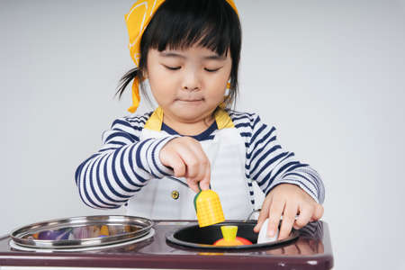 Pretty asian thai kid play role as a chef wearing yellow bandage cooking food with stove in kitchen.