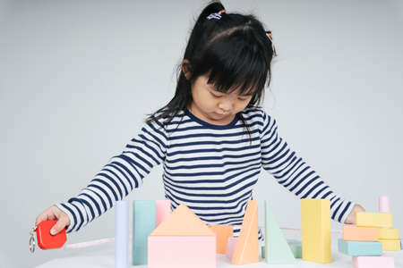 Pretty asian thai kid woman playing with toy block.