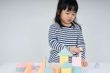 Pretty asian thai kid woman playing with toy block shape.