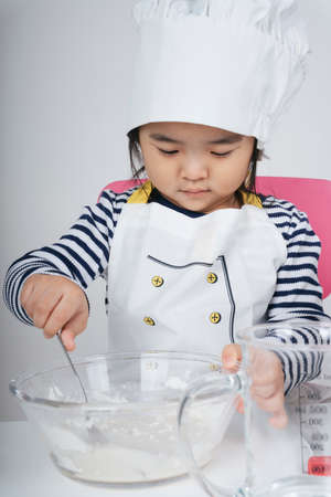 Pretty asian thai kid play role as a chef mixing flour and water into glass bowl in kitchen. 免版税图像