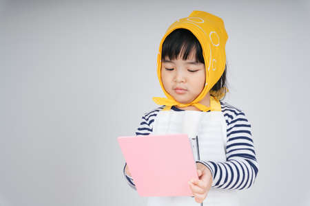 Pretty thai kid play role as a waitress wearing yellow bandage taking order from customer with paper and pen.