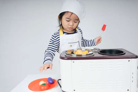 Pretty asian thai kid play role as a chef wearing yellow bandage cooking in kitchen.