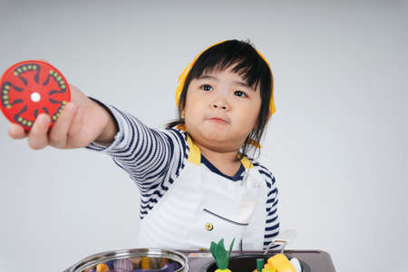 Pretty asian thai kid play role as a chef wearing yellow bandage holding slice of tomato cooking in kitchen.
