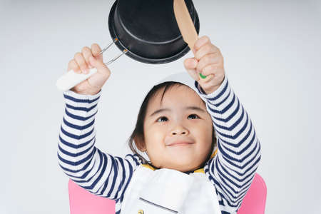 Pretty asian thai kid play role as a chef working at cooker station with boil pot. 免版税图像
