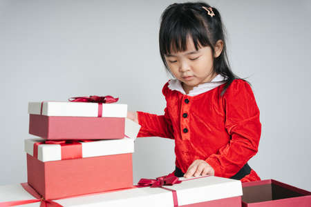 Pretty asian thai kid woman in santa claus uniform with christmas gift box to celebrate snow festival.