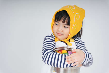 Pretty asian thai kid play role as a waitress wearing yellow bandage hugging cooking pot isolate over white background.