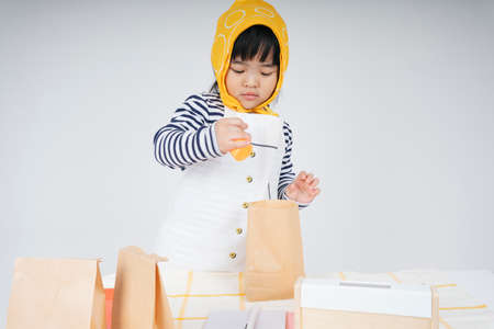 Pretty asian thai kid play role as a waitress wearing yellow bandage packing food in paper bag. 免版税图像