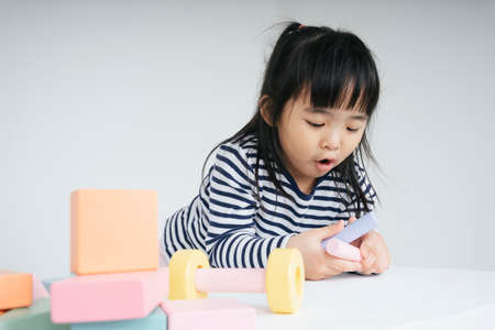 Pretty asian thai kid woman playing with toy block at home.