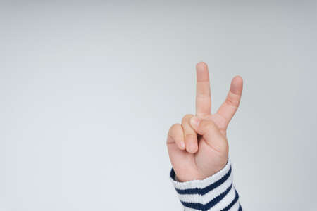 Kid hand with victory two fingers gesture isolate over white background.