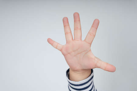 Kid hand with five fingers gesture isolate over white background.