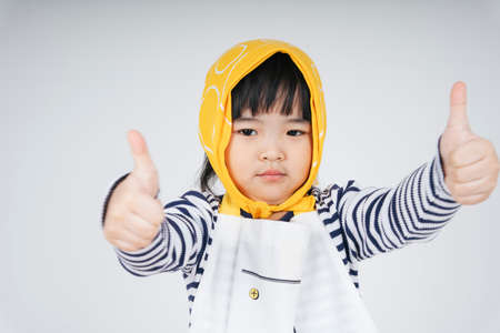 Pretty asian thai kid wearing yellow bandage show thump up gesture isolate over white background.