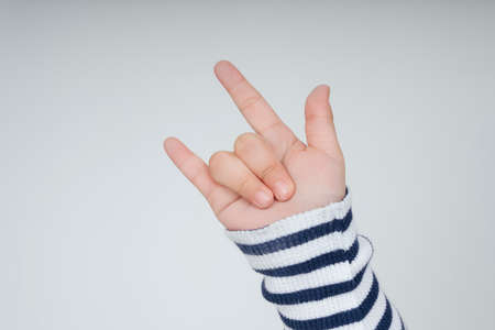 Kid hand with I love you gesture isolate over white background. 免版税图像