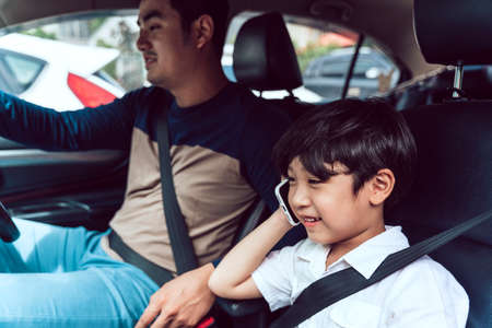Asian son talking on the phone in the car while father driving. Stock Photo