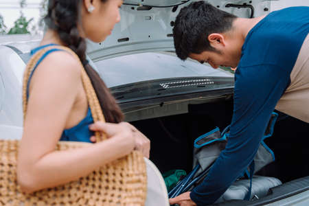 Asian man packing stuff and put it back at trunk car. Road trip with family.