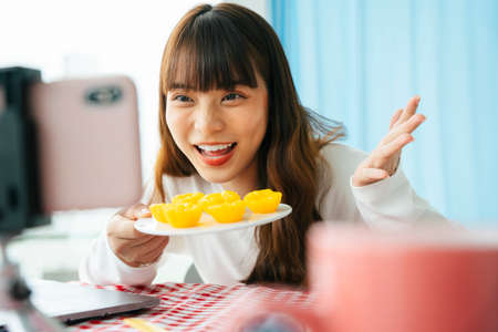 Young asian dark hair woman doing thai dessert food review with golden cake infront of smartphone camera.