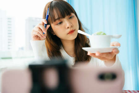 Young asian dark hair woman food reviewer examine thai dessert before writing a review.