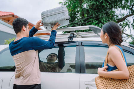Asian couple prepre for road trip. Man putting suitcase bag on car roof. Road trip with family. Stock fotó - 155351972