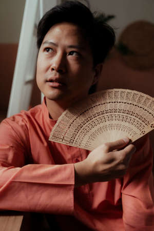 Nontraditional asian guy hold the traditional fan as the accessory which could refine his beauty.