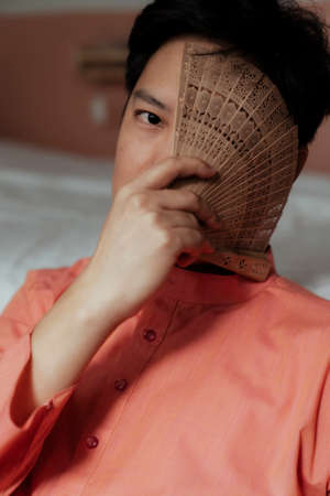 A black hair gay look at the camera with one eye while he cover another his eye with folding fan. Archivio Fotografico
