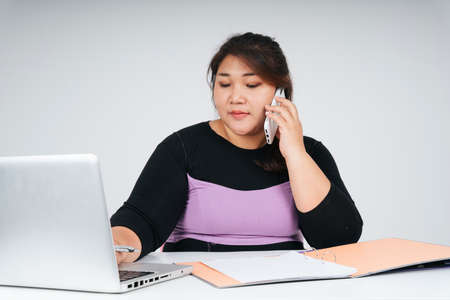 Asian chubby business woman working on laptop and talking on the phone with customer Banque d'images