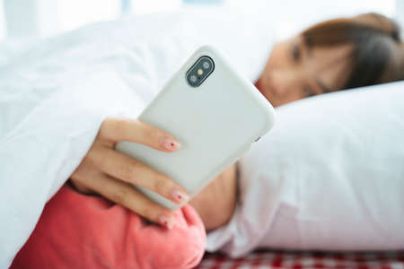 Young asian dark hair woman laying on a bed using smartphone in the morning.