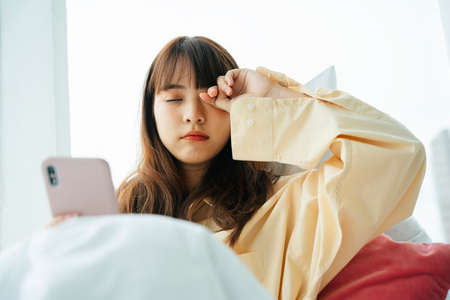 Sleepy young asian dark hair woman wake up on a bed and use smartphone in the morning.