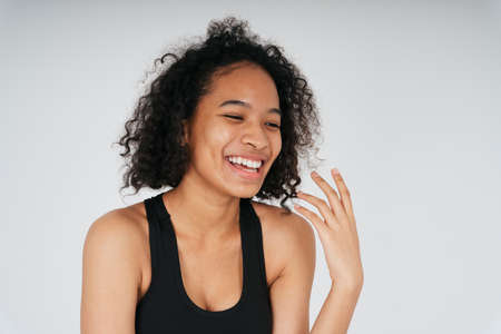 Portrait of cheerful and laugh african woman in black sport bra on white background.