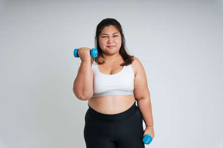 Healthy fat woman in white sport bra exercise with dumbbells on isolate on white background.