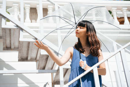 Young asian woman traveler wearing blue dress holding transparent umbrella standing on stair outdoors in sunny day.