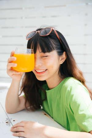 Cheerful young asian woman traveler wearing green shirt and sunglasses enjoy drinking healthy orange juice. 写真素材