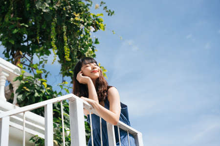Young asian woman traveler wearing blue dress at balcony in sunny day. 写真素材