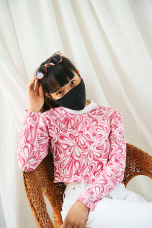 Young asian woman in pink shirt wear sunglasses and mask sitting on a chair. 写真素材