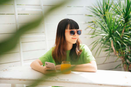 Young asian woman traveler wearing sunglasses sitting at bar with orange juice and using smartphone outdoors at yard. 写真素材