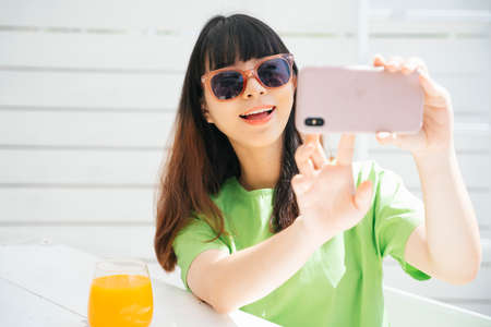 Beautiful young asian woman traveler wearing sunglasses holding glass of orange juice doing vlog with smartphone for social media.